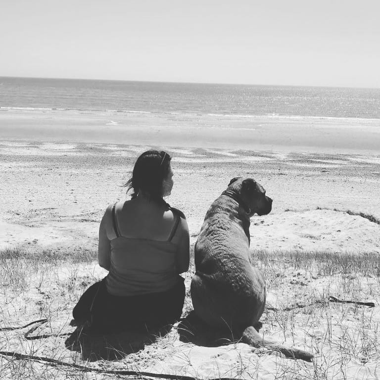 Amber, a dog walker, sitting at the beach with a big dog looking at the sea